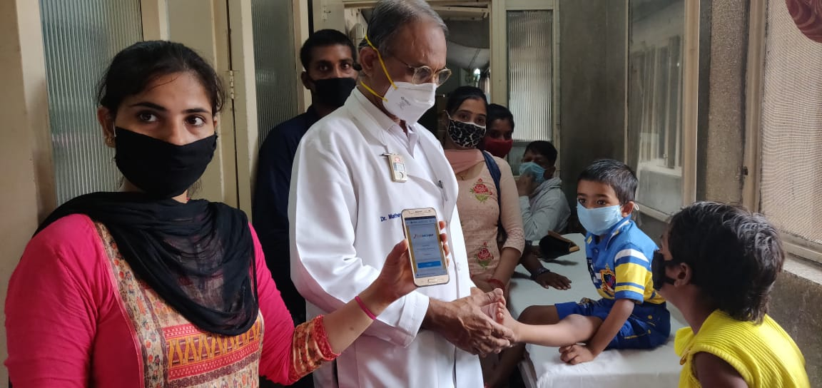 Dr Mathew Nishchay using the Nischay Web Application on his Phone while treating patients